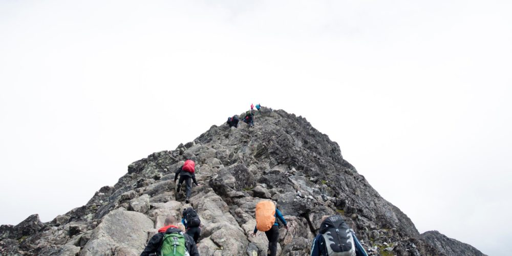 4 People climbing up a mountain