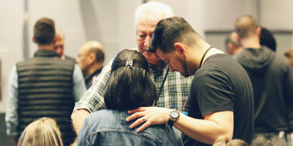 An older man praying for a younger couple